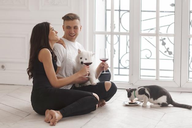 Uma garota e um cara sentados em uma nova casa no chão com seus animais de estimação