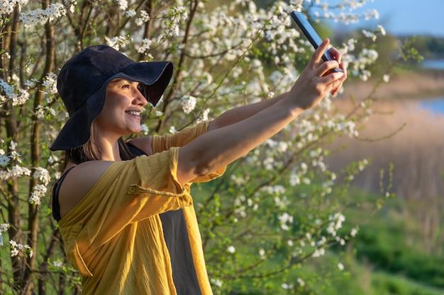 Uma garota elegante com um chapéu faz uma selfie ao pôr do sol, perto de árvores floridas na floresta.