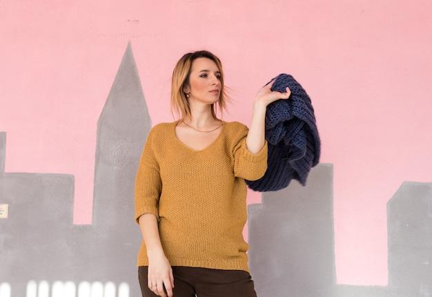 Uma garota elegante e elegante em roupas da moda vintage com uma bolsa posa contra a parede.