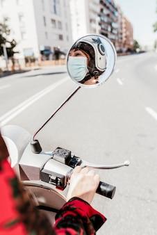 Uma garota elegante e jovem aprende a andar de moto com máscara facial