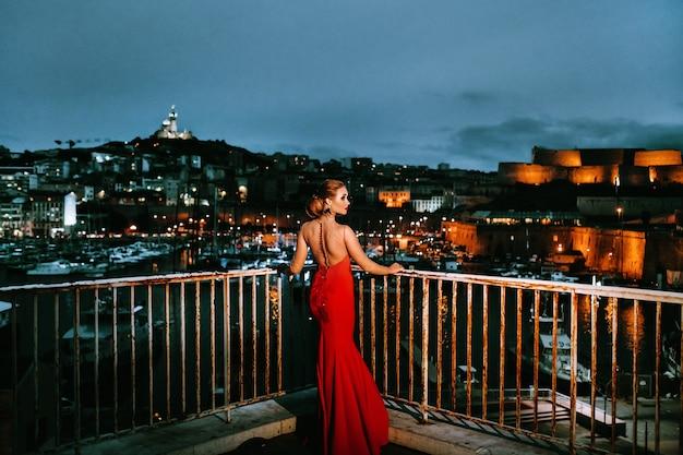 Uma garota elegante em um vestido de noite vermelho nas ruas da cidade à noite de marseille. uma mulher em um vestido de noite vermelho na frança.