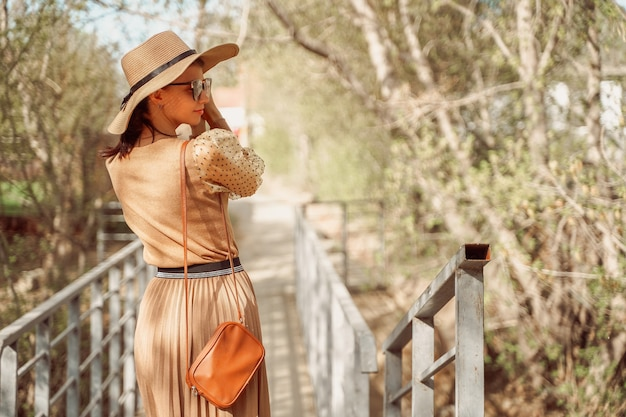 Uma garota elegantemente vestida com um vestido bege romântico com uma saia plissada e um chapéu de palha caminha ao longo da ponte.
