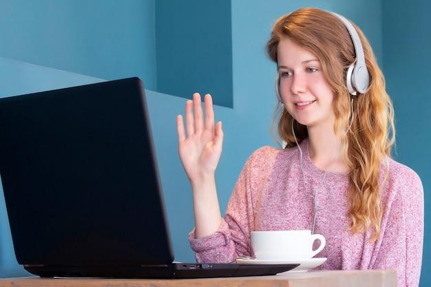 Uma garota em fones de ouvido se comunica via chat por vídeo em um laptop.