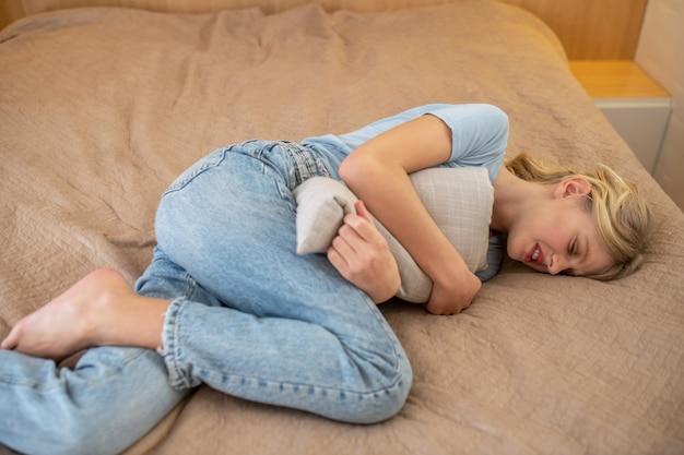 Uma garota em seus dias críticos e sofrendo de dor