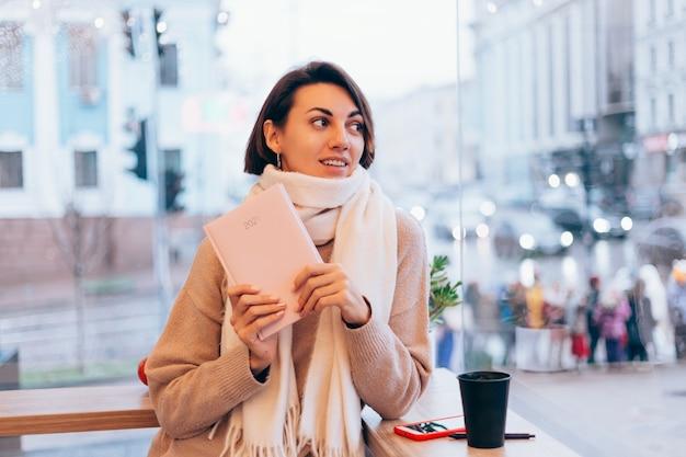 Uma garota em um café aconchegante se aquece com uma xícara de café quente