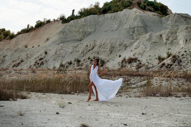 Uma garota em um longo vestido branco com flores no cabelo contra o fundo da areia branca da praia e grama seca