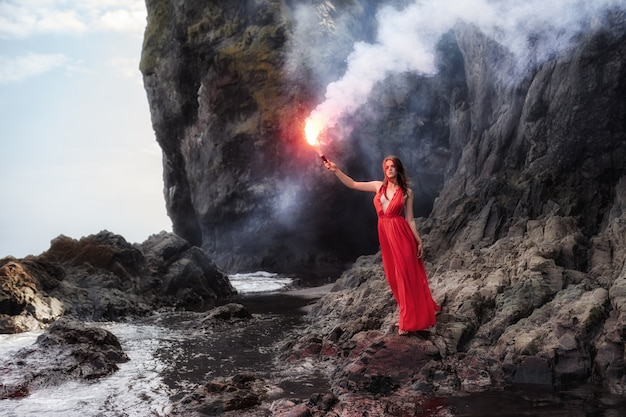 Uma garota em um longo vestido vermelho e com uma tocha na mão caminha ao longo da costa rochosa do oceano