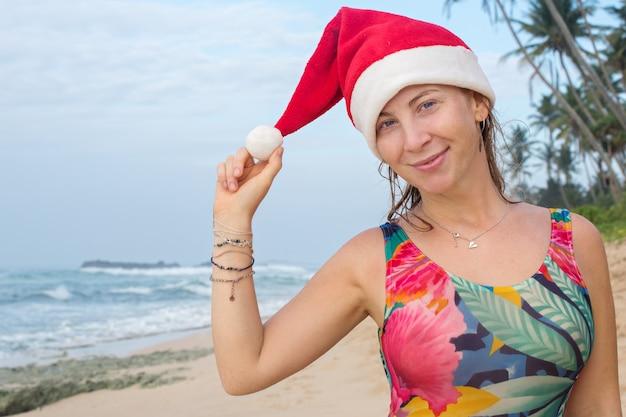 Uma garota em um maiô e chapéu de papai noel no oceano