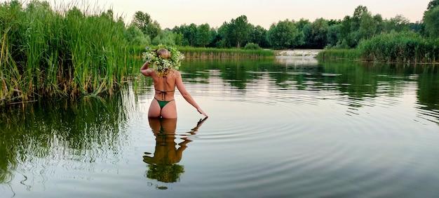 Uma garota em um maiô e com um buquê de flores na cabeça está na água