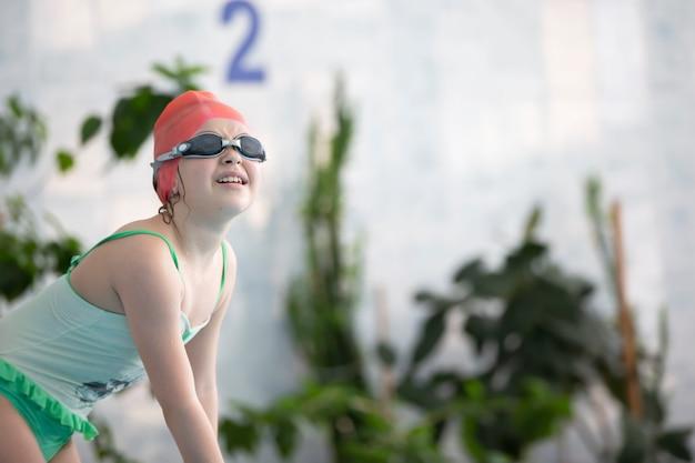Uma garota em um maiô e uma touca de natação com óculos na piscina esportiva.