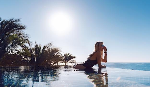 Uma garota em um maiô fechado e óculos escuros sai da água em uma piscina panorâmica e gosta de se bronzear. conceito de férias.
