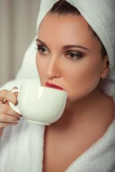 Uma garota em um manto branco após um banho toma café de sua xícara no quarto