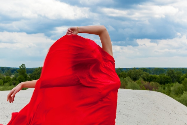 Uma garota em um pano vermelho na areia posa para um fotógrafo no contexto de um céu nublado. tecido vermelho ao vento abraça a figura da menina.