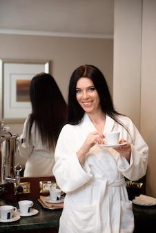 Uma garota em um roupão branco está descansando e bebendo uma xícara de café ou chá, aproveitando o fim de semana de bem-estar