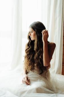 Uma garota em um roupão senta-se perto de uma janela