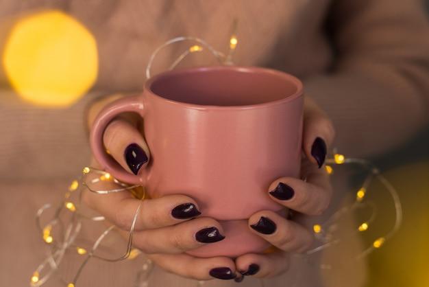 Uma garota em um suéter rosa delicado com manicure escuro segura uma caneca de bebida quente nela com um garl amarelo. atmosfera de natal, luzes de calor de um garl