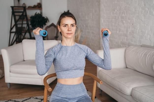 Uma garota em um terno cinza balança os bíceps com halteres smart fitness em casa esportes online conceito de fitness doméstico