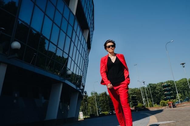 Uma garota em um terno vermelho está no fundo de um edifício moderno na cidade