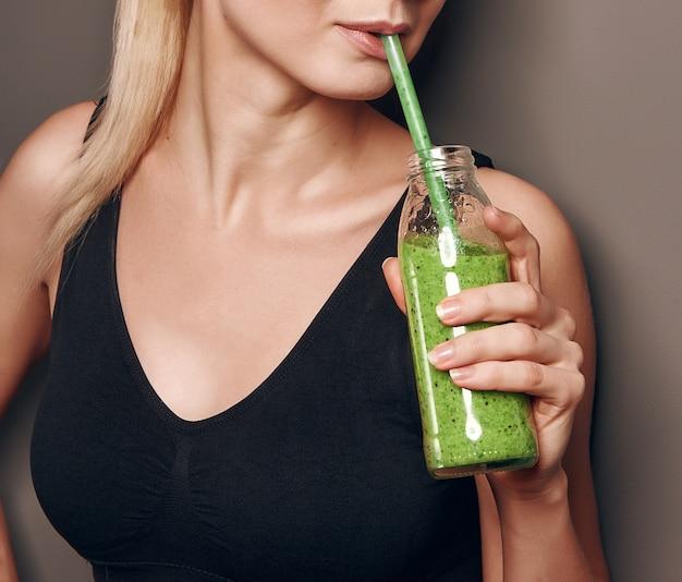 Uma garota em um top preto esportes tem um pote de smoothies de vegetais nas mãos