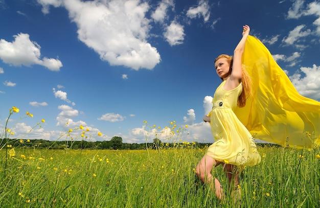 Uma garota em um vestido amarelo posa com as mãos para cima em um campo verde com um pano de seda nas mãos.