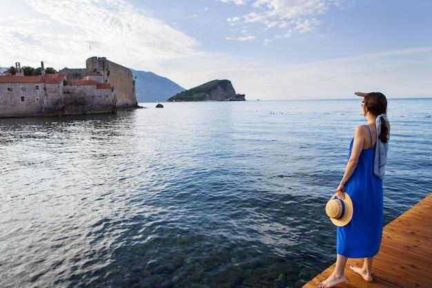 Uma garota em um vestido azul com um chapéu de palha fica em um píer de madeira perto do mar. ao fundo está a antiga cidade medieval de montenegro, em budva.