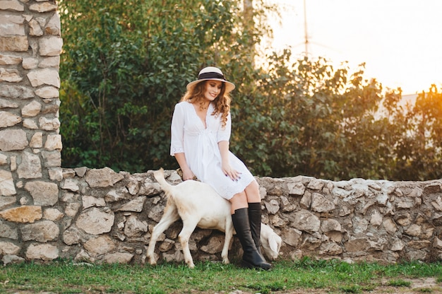 Uma garota em um vestido branco anda com uma cabra na natureza.