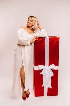 Uma garota em um vestido branco com um enorme presente vermelho sobre um fundo branco sorri.
