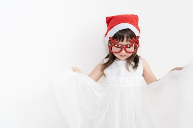 Uma garota em um vestido branco fica contra um fundo claro. o bebê está segurando a saia nas mãos.