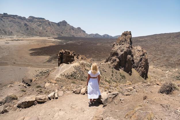 Uma garota em um vestido branco fica na cratera do vulcão teide. tenerife, ilhas canárias. Foto Premium