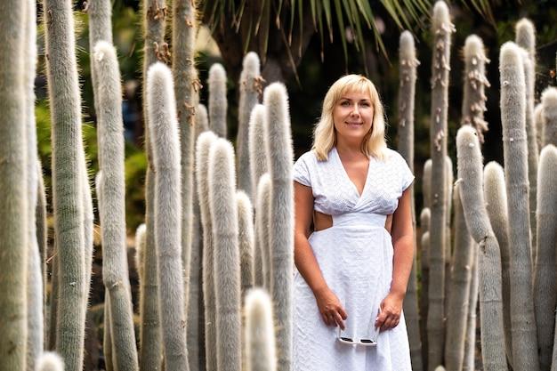 Uma garota em um vestido branco no fundo de enormes cactos na ilha de tenerife