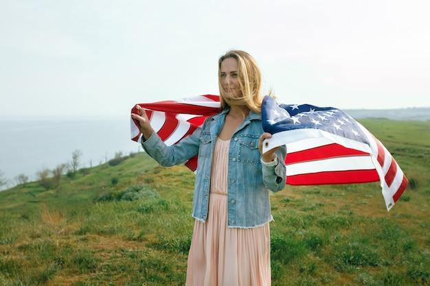 Uma garota em um vestido coral e uma jaqueta jeans segura a bandeira dos estados unidos nas mãos. 4 de julho dia da independência.