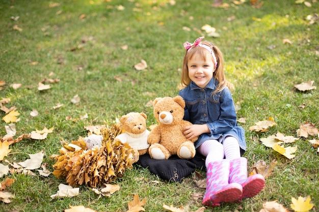 Uma garota em um vestido de brim se senta e sorri em uma strava com ursos