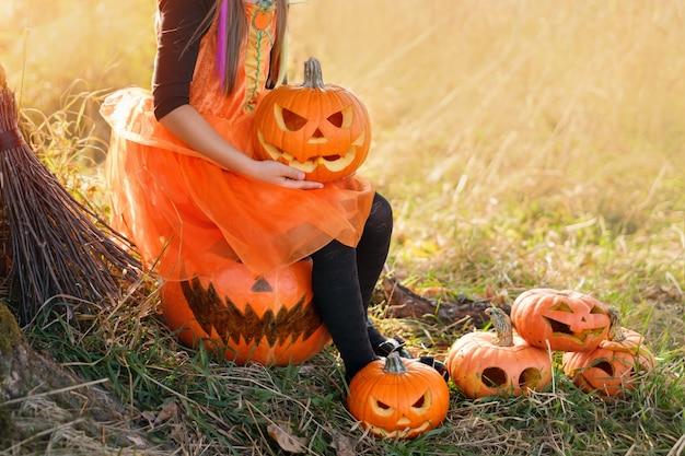 Uma garota em um vestido de carnaval segura uma abóbora com um sorriso maligno esculpido nas mãos