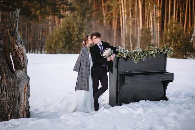 Uma garota em um vestido de noiva e um jovem estão de pé ao lado do piano. fotografia de inverno