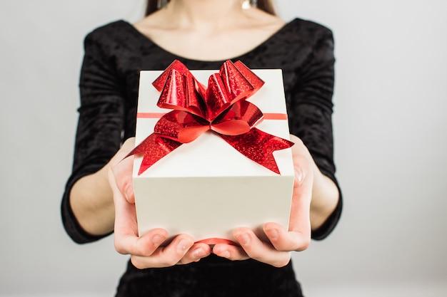 Uma garota em um vestido preto segura um presente branco com um laço vermelho.