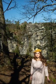 Uma garota em um vestido rosa e um chapéu no fundo das montanhas e desfiladeiros na saxônia suíça, alemanha, bastei.