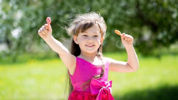 Uma garota em um vestido vermelho com doces nas mãos dela.