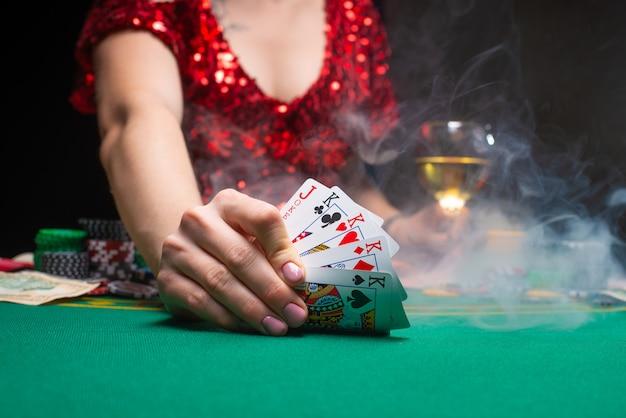 Uma garota em um vestido vermelho joga pôquer em um cassino noturno