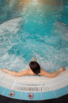 Uma garota em uma banheira de hidromassagem, piscina no centro de spa, tratamentos de água