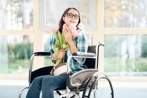 Uma garota em uma cadeira de rodas com flores nas mãos dela.