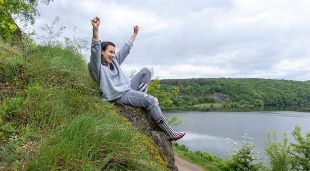 Uma garota em uma caminhada escalou uma montanha em uma área montanhosa e se alegra.