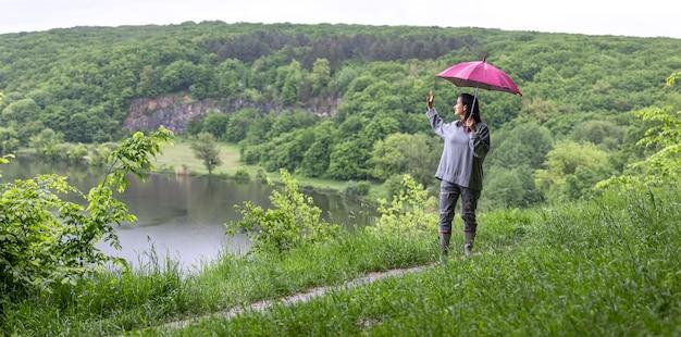 Uma garota em uma caminhada na floresta sob um guarda-chuva entre as montanhas perto do lago.