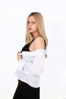 Uma garota em uma camisa branca e uma camiseta preta posa para a câmera. imagem em um fundo branco