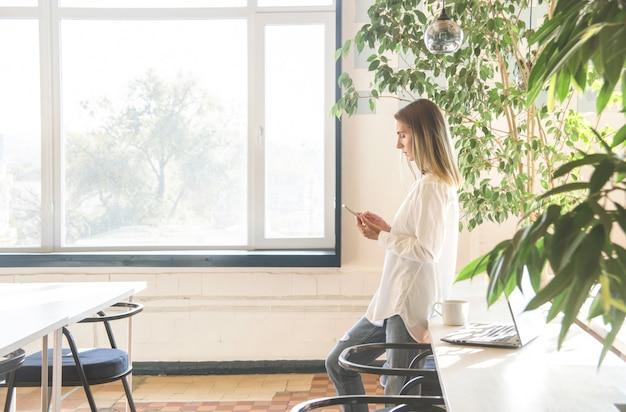 Uma garota em uma camisa branca está olhando para smartphone entre trabalho freelancer.