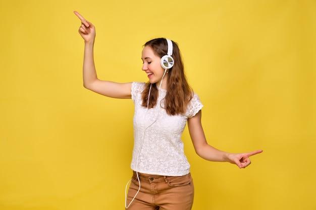 Uma garota em uma camiseta branca e calça jeans marrom em um fundo amarelo relaxa e dança ouvindo música em fones de ouvido brancos.