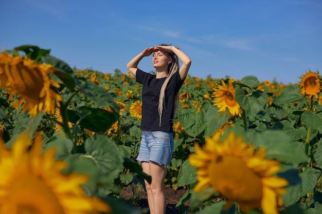 Uma garota em uma camiseta preta e shorts jeans está em um campo com girassóis e olha para o ...