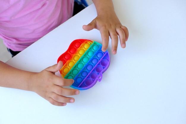 Uma garota em uma camiseta rosa brinca com um brinquedo da moda estourá-lo. o brinquedo sensorial anti-stress colorido fidget push pop nas mãos das crianças, pode ser usado para treinar com pessoas autistas.