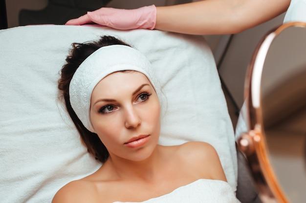 Uma garota em uma consulta médica, olhando no espelho, um leve sorriso no rosto da cliente
