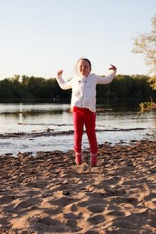 Uma garota em uma jaqueta branca e calça rosa pula na areia na praia na margem do rio durante o pôr do sol.