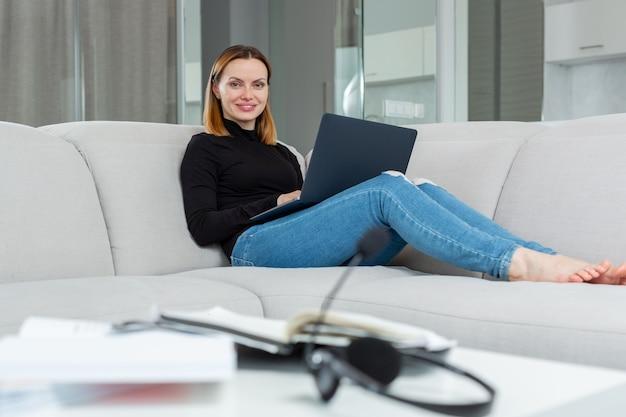 Uma garota em uma jaqueta preta e jeans senta em casa no sofá e trabalha atrás de um laptop, sorri e olha para a câmera foto de alta qualidade